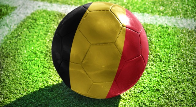 football ball with the national flag of belgium lies on the green field near the white line