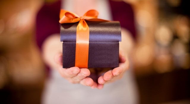 Sales person offering a wrapped chocolate box. Selective focus.